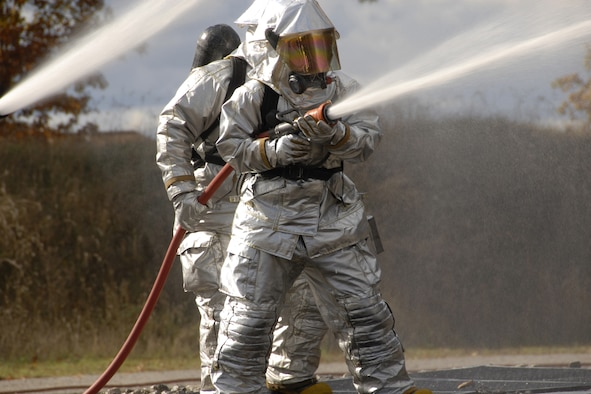 Staff Sgt. Keith Vasicek and Airman 1st Class Tony Pastrone battle a controlled fire during an aircraft crash site drill Oct. 18 at CRTC Training Base Alpena Mich.  Vasicek and  Pastone are Air force National Guard members attached to the 127th Fire Department Selfridge ANGB, Mich.  Vasicek and  Pastrone are both active fire fighters in both their civilian and military occupations. Combat Readiness Training is key to their alertness and spontaneity in emergency situations.  (U.S. Air Force photo by Tecnical Sgt. David S. Kujawa)