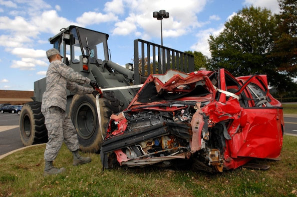 Senior Airman Brian Hitlt, 11th Logistics Readiness Squadron, unties a wrecked car Oct. 23 in Bolling's base exchange and commissary parking lot. The car is a visual aid used by the 11th Wing Safety Office to remind people to practice vehicle safety as part of the Fall Safety Campaign. (U.S. Air Force photo by Airman Tim Chacon)