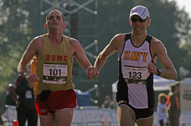 Cpl. Thomas Kunish, 28, and Lt. Cmdr. Timothy Fahey, 34, cross the finish line together at the 33rd Marine Corps Marathon with a time of 2:30:12. Kunish, the first Marine to cross the finish line, said he attributed part of his personal record-setting performance to Fahey for helping him 'run the best race' of his life.