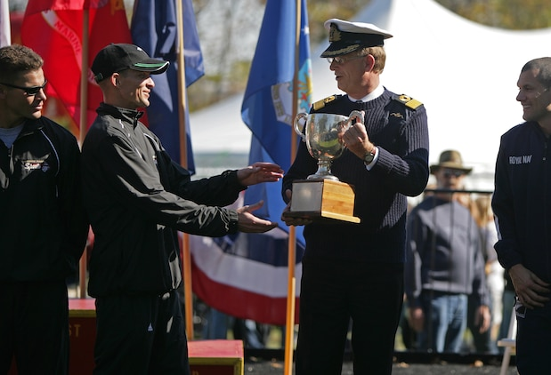 Cpl. Thomas Kunish, a fiscal clerk with 3rd Marine Logistics Group, waits to receive the Challenge Cup from a British Royal Navy/Marine representative during an awards ceremony after the 33rd Marine Corps Marathon Oct. 26. The Challenge Cup competition between the two services began in 1978.
