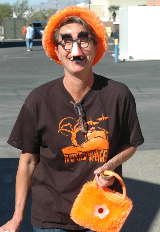 """Barb Gavre, wing family readiness coordinator and Haunted Hangar chairperson, enjoys another successful morale and family event. """"I want to thank all of the volunteers and the people who donated pumpkins, cakes, candy, time and money to make Haunted Hangar a fun and memorable experience for wing families,"""" she said. (Air National Guard photo by Capt. Gabe Johnson)"""