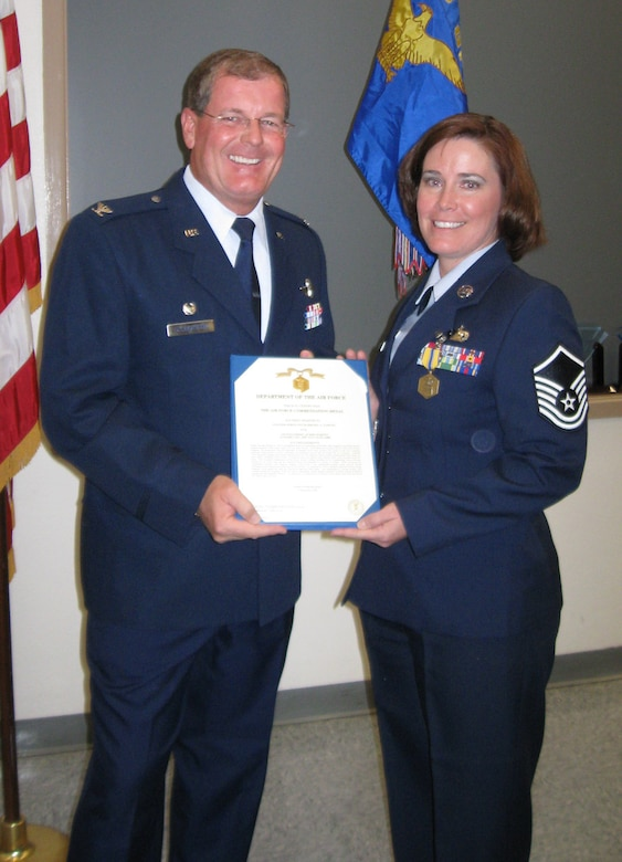 Master Sgt. Barbara Tarvin, 926th Group Career Advisor, receives a Commendation Medal during Commander's Call on Oct. 25.