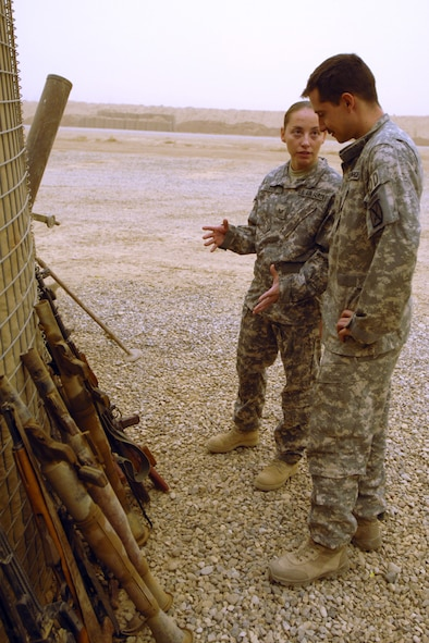 """Staff Sergeant Angela """"O"""" Olguin and Senior Airman Joshua Brum, 506th Air Expeditionary Group Explosive Ordnance Disposal flight technicians, discuss the disposal of insurgent weapons and ordnance Sept. 15. Both Airmen are forward deployed to FOB McHenry where they are embedded with soldiers of the Army's 10th Mountain Division. Both Airmen are also deployed from Nellis Air Force Base, Nev. (U.S. Air Force photo/Tech. Sgt. Jeff Walston)"""