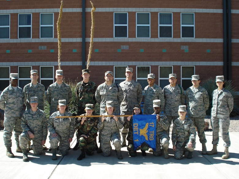 Technical Sergeant Roberto Oregon, at center with dark rope over left shoulder, poses with Airmen in technical training next to the 17th Training Group Detachment 1 headquarters building at Fort Huachuca, Ariz. (U.S. Air Force photo by Staff Sgt. Luis Chavez)