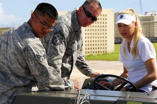 ANDERSEN AIR FORCE BASE, Guam - Senior Master Sgt. Paul Cornell and Senior Airman Michael O'Rourkeu, 36th Maintenance Squadron, explains to Ms. Anna Kournikova how to correctly operate a MHU Bomblift here Oct. 29. Ms. Kournikova was on Guam for a two-day tour sponsored by the USO of Andersen and Naval Base Guam.  (U.S. Air Force photo by Airman 1st Class Nichelle Griffiths)