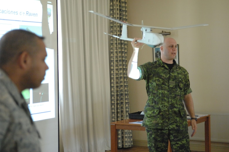 Canadian army Maj. Brian Nekurak (right) an officer in the foreign exchange program, demonstrates the use and capabilities of the small, unmanned aerial system Oct. 29 while Master Sgt. Edward Nin translates Major Nekurak's words into Spanish at Quintero Air Base, Chile during Operation Southern Partner. Operation Southern Partner is an in-depth, two-week subject matter exchange emphasizing partnership, cooperation and sharing of information with partner nation Air Forces  in Latin America. 