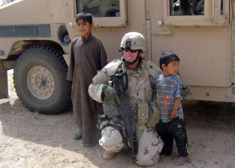 SOUTHWEST ASIA -- Under a very watchful eye from his team, Tech. Sgt. Trevor Dunn poses with some local children during a deployment to Southwest Asia. Sergeant Dunn recently won the Air Force Space Command Security Forces Individual Award for Outstanding Security Forces Support Staff Non-Commissioned Officer. (Courtesy photo)