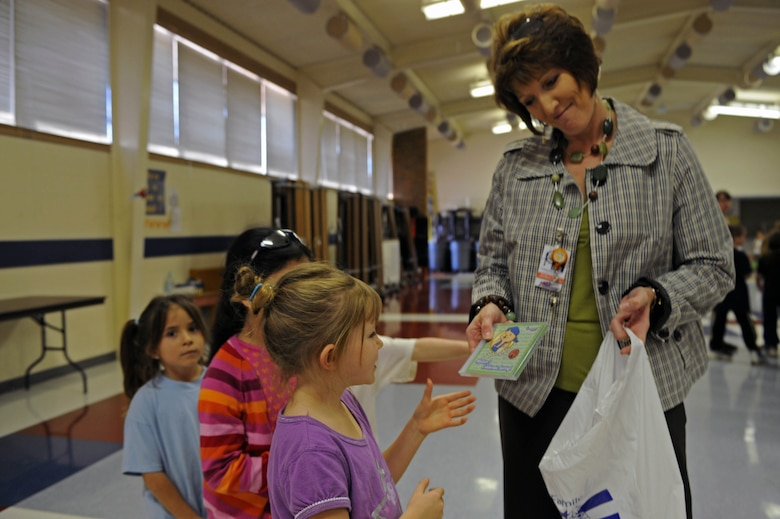 "Michelle Henrich, principal of Badger Clark Elementary, hands out Sammy Rabbit cd's to students at Badger Clark Elementary, S.D., Oct. 30. ""From every dollar save a dime,"" was one of Sammy Rabbit's main messages expressed to the students. (U.S. Air Force photo by Airman Corey Hook)"