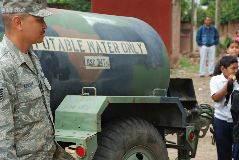 SOTO CANO AIR BASE, Honduras - Air Force Tech. Sgt. Ramano Cedillos, deployed from the Phoenix Air National Guard, assists people in getting clean water Oct. 29. After the water is filtered, it is placed in 500-gallon water buffalos so people have free access to the purified water. (U.S. Army photo by Specialist Ethan Anderson)
