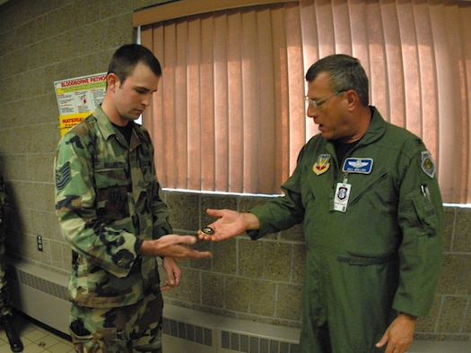 U.S. Air Force Col. William Mullins, right, presents a special unit compliance inspection coin to Tech. Sgt. Levi J. Heller, of the 119th Security Forces Squadron, in recognition of the outstanding work he has done in the combat arms training and maintenance area of the North Dakota Air National Guard. Heller is responsible for procuring, storing and tracking weapons parts for all weapon systems on the installation, which was reported as 'the best seen to date' by the unit compliance inspection team.