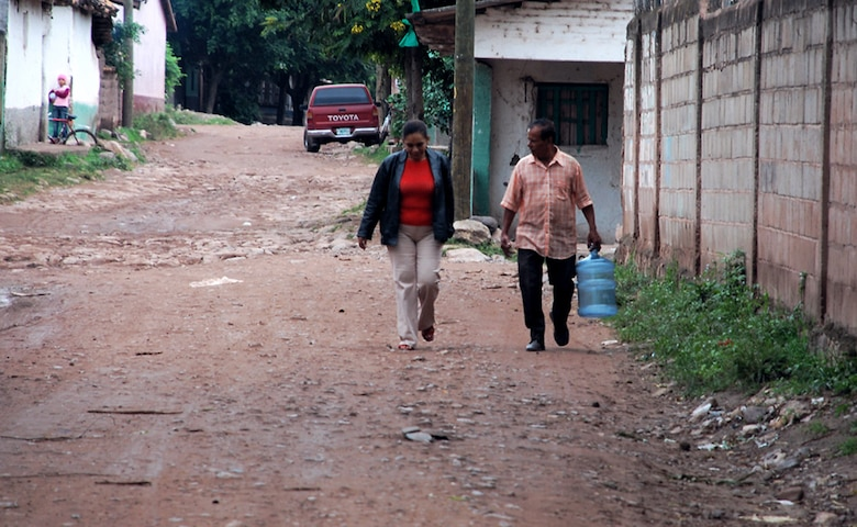 A family walks down the road to get the free purified water provided by Joint Task Force-Bravo members Oct. 29 at La Paz, Honduras. Before JTF-Bravo members offered to purify the well water affected by the flooding, the community had to have water trucked in at great expense to them. (U.S. Air Force photo/Staff Sgt. Joel Mease)