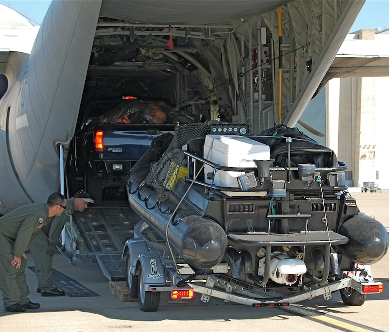 Chief Master Sgt. Charles Dehart (black hat), a loadmaster from the 146th Airlift Wing and a PJ from the 129th Rescue Wing spot the tires of an on-boarding truck filled with rescue equipment.  PJs from the 129th Rescue Wing loaded various equipment in preparation of the possible aftermath of Hurricane Gustav. (U.S. Air Force photo by Staff Sgt. Jill Jamgochian)