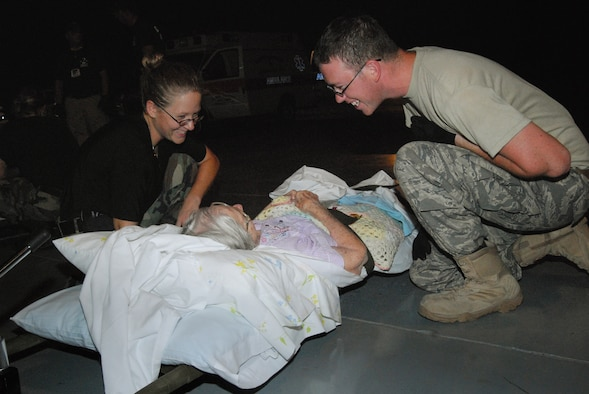 Tech. Sgt. Krystal Marks, 43rd Aerospace Medicine Squadron and Senior Airman Payden Forkum, 43rd Medical Operations Squadron, provide care to an elderly woman at the Lakefront Airport in Louisiana August 31. (U.S. Air Force photo/Airman 1st Class Mindy Bloem)