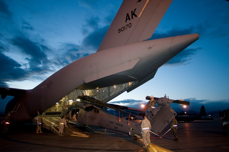 KULIS AIR NATIONAL GUARD BASE, Alaska -- In the early morning hours of Sept. 1, 2008, Alaska Air National Guardsmen from the 176th Logistics Readiness Squadron maneuver an HH-60 Pave Hawk helicopter onto the loading ramp of a C-17 strategic airlift jet. The helicopter is one of two the Alaska Air National Guard?s 176th Wing is deploying to the Gulf Coast region to support possible search-and-rescue operations expected in the wake of Hurricane Gustav. Approximately 30 wing members have deployed to the region as well. Alaska Air National Guard photo by Lt Col Tim O'Brien.