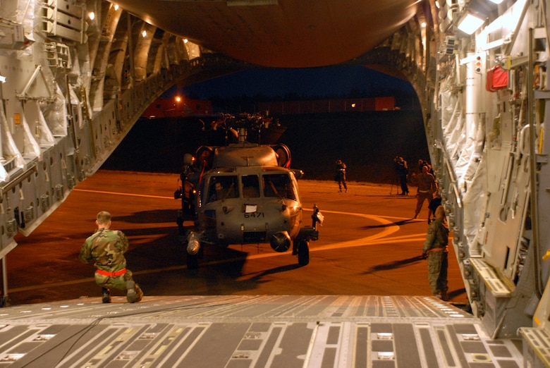 KULIS AIR NATIONAL GUARD BASE, Alaska -- In the early morning hours of Sept. 1, 2008, Alaska Air National Guardsmen from the 176th Logistics Readiness Squadron maneuver an HH-60 Pave Hawk helicopter onto the loading ramp of a C-17 strategic airlift jet. The helicopter is one of two the Alaska Air National Guard?s 176th Wing is deploying to the Gulf Coast region to support possible search-and-rescue operations expected in the wake of Hurricane Gustav. Approximately 30 wing members have deployed to the region as well. Alaska Air National Guard photo by 2nd Lt. John Callahan.