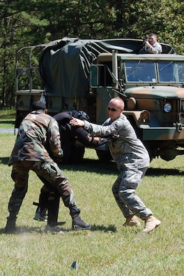 """Students in the U.S. Air Force Expeditionary Center's Phoenix Raven Training Course battle an """"agressor"""" during an evaluation session for the Raven course on a Fort Dix, N.J., range Aug. 20, 2008.  Raven training is taught by the Center's 421st Combat Training Squadron at Fort Dix.  It gives security forces Airmen specialized training in aircraft security, verbal judo and self defense.  (U.S. Air Force Photo/Tech. Sgt. Scott T. Sturkol)"""