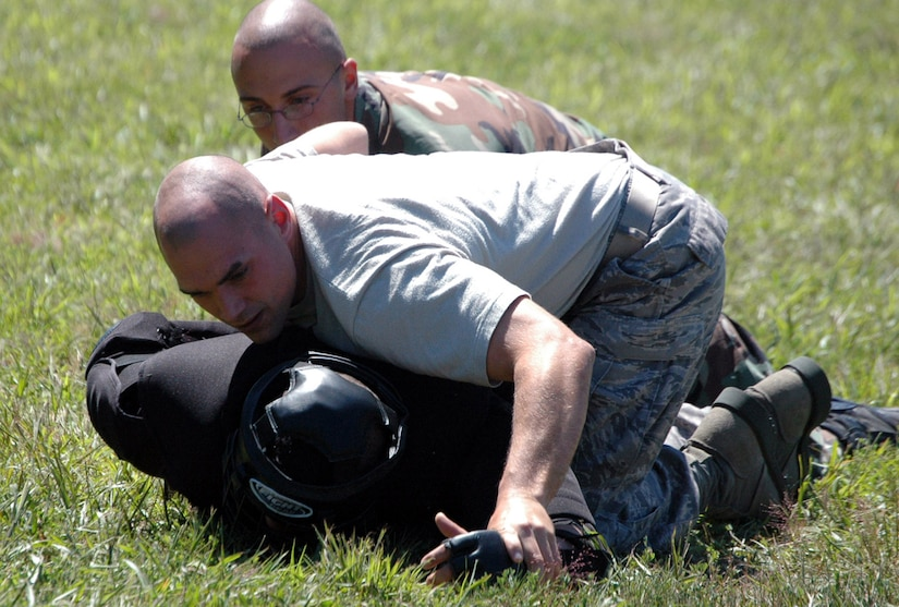 """Students in the Air Force Phoenix Raven Training Course restrain an """"aggressor"""" during an evaluation session in the course on a Fort Dix, N.J., range Aug. 20, 2008.  The course, taught by the U.S. Air Force Expeditionary Center's 421st Combat Training Squadron, trains security forces Airmen to become Ravens where they specialize in protecting Air Force aircraft in austere environments.  (U.S. Air Force Photo/Tech. Sgt. Scott T. Sturkol)"""