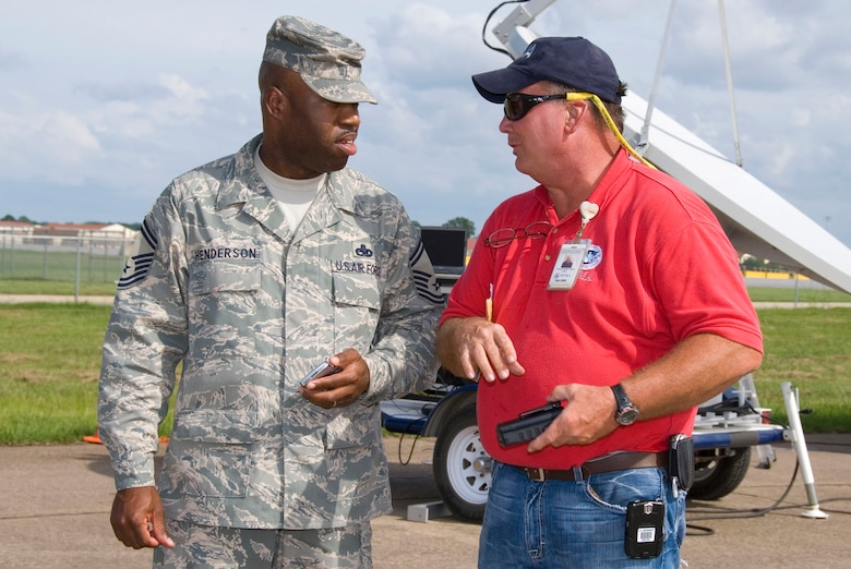 Senior Master Sgt. Terence Henderson, the Maxwell Air Force Base, Ala., Federal Emergency Management Agency liaison, talks with Ronnie Banes, a FEMA site manager, about staging efforts on the base flightline.  (U.S. Air Force photo/Jamie Pilcher)