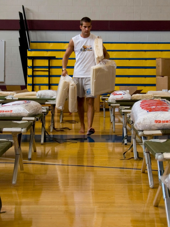 Jacob Weir, a contractor at Maxwell Air Force Base, Ala., sets up bedding Aug. 31 in the base gymnasium which serves as a temporary shelter for any evacuees arriving from the Gulf coast during Hurricane Gustav.  (U.S. Air Force photo/Jamie Pilcher)