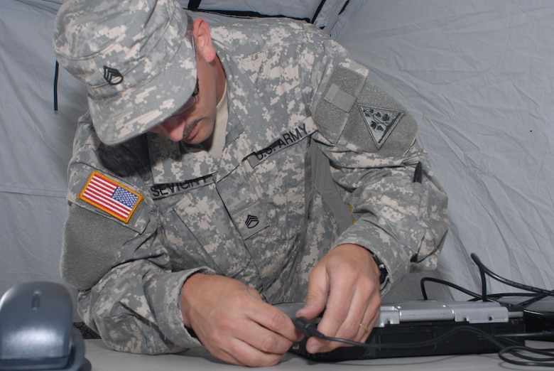 Army National Guardsman, Staff Sgt. Ted Sevigny, Joint Forces Headquarters, Hartford, Connecticut, connects a laptop to the Joint Incident Site Communication Capability (JISCC) system during the June 5, 2008 deployed training exercise at Camp Rell, Niantic, Connecticut.  Connecticut Air and Army National Guard units train together on deploying the JISCC equipment, which allows federal, military, state and local emergency services to coordinate disaster relief efforts with real-time communication. (U.S. Air Force photo by Staff Sgt. Nicholas A. McCorkle)