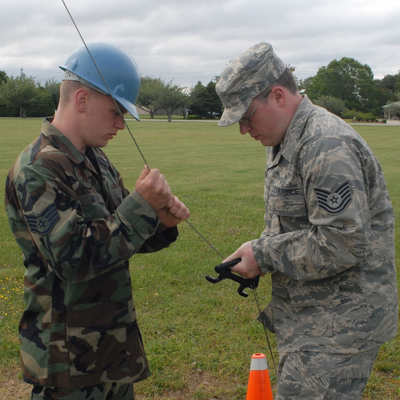 Tech. Sgt. Eric W. Dunn, 103rd Air Operations Group and Staff Sgt. Ryan J. Brown, 103rd Communication Squadron, Connecticut Air National Guard, anchor an antennae cable during the June 5, 2008 Joint Incident Site Communication Capability (JISCC) deployed training exercise at Camp Rell, Niantic, Connecticut. Simulated emergency service relief efforts are communicated through the JISCC system via satellite transmission, linking four mobile command posts belonging to various local authorities within the state. (U.S. Air Force photo by Staff Sgt. Nicholas A. McCorkle)