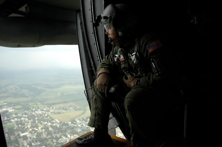 Tech. Sgt. Eric Valdez, 129th Rescue Wing loadmaster, scans the ground in Louisiana for civilian victims in need of rescue Sept. 2.  More than 80 Airmen from the 129th RQW deployed to Ellington Field, Texas, as part of Joint Task Force 129, which supported Hurricane Gustav rescue operations. Air National Guardsmen from the 106th Rescue Wing, Gabreski Airport, N.Y., and 176th Wing, Kulis Air National Guard Base, Alaska, were also part of the rescue task force. (U.S. Air Force photo by Tech. Sgt. Ray Aquino)