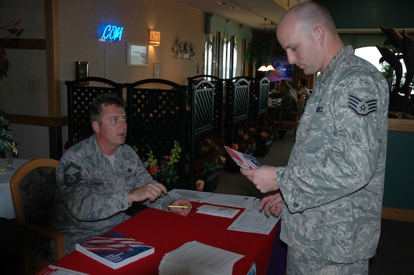 Staff Sgt. Christopher Clark gets information on registering to vote from Senior Master Sgt. Jeffrey Hebner at the Riverside Dining Facility September 2 during Armed Forces Voting Week. Tables were set up today in the Dining Facility and other public areas, such as the Base Exchange, where troops could find out about how to receive absentee ballots from unit Voting Assistance Officers. (U.S. Air Force photo by Airman 1st Class David Dobrydney)
