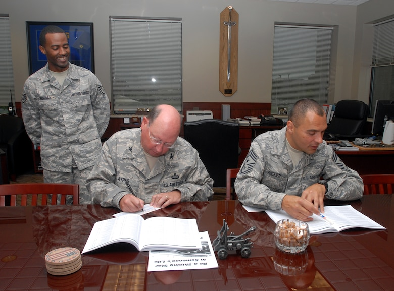 Colonel Richard Ayres (center), 17th Training Wing commander, and Chief Master Sgt. Frederick Ricker (right), 17 TRW command chief master sergeant, sign up for the 2008 Combined Federal Campaign with the help of Staff Sgt. Christopher Morgan, a campaign volunteer. (U.S. Air Force photo by Paul Martin)
