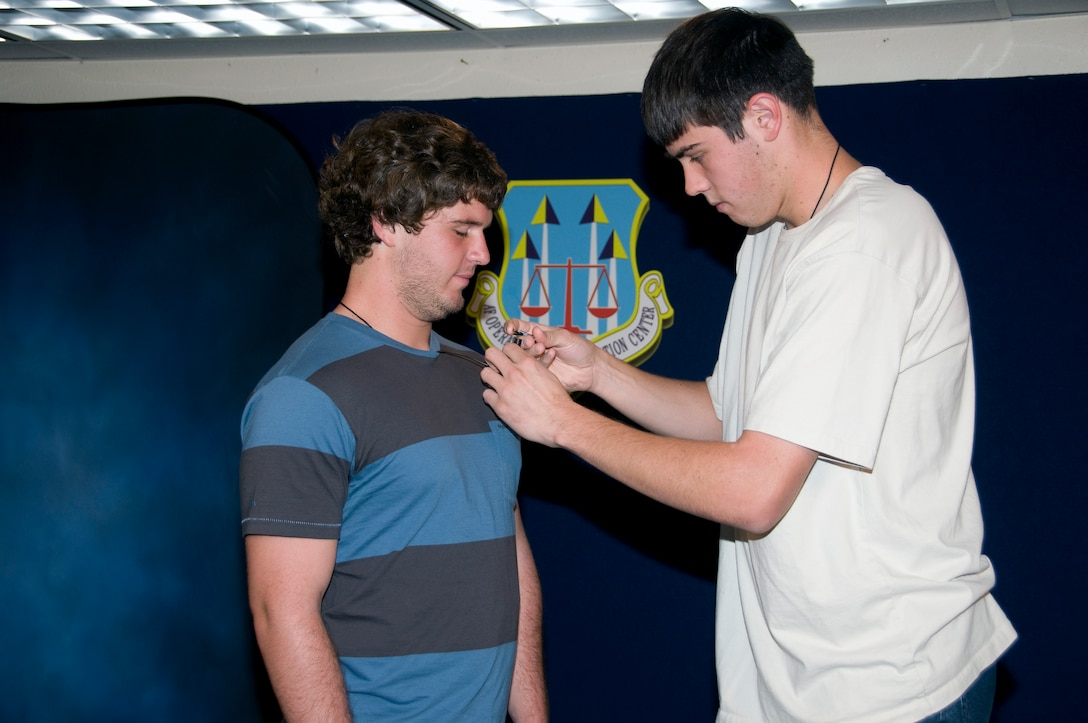 Calum Murray, left, a student intern with the Air Force Operational Test and Evaluation Center, waits as Ethan Halliday, another AFOTEC student intern, attaches a microphone in preparation for an interview. Both students are part of the AFOTEC program that exposes selected University of New Mexico students to the Air Force and to government service.