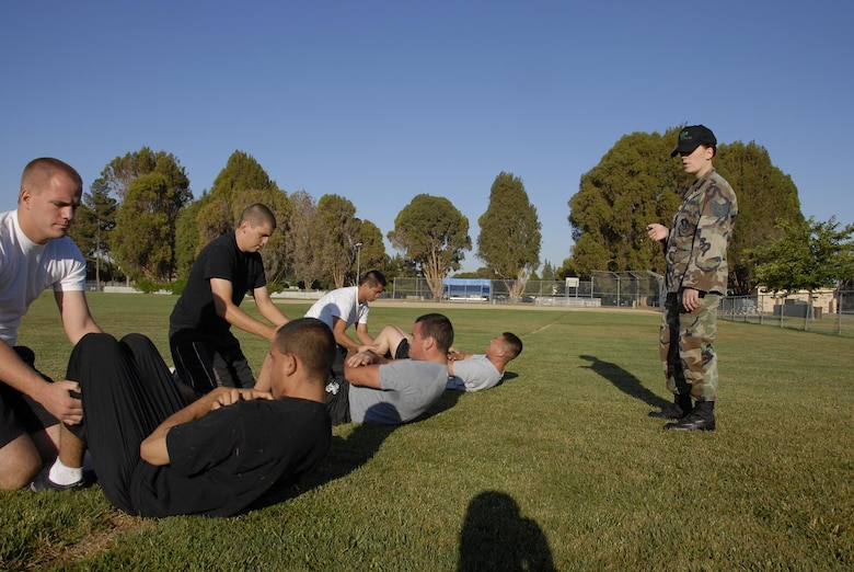 Tech. Sgt. Rachel Taylor, Student Flight Non-Commissioned Officer, times the Student Flight's sit-up exercises.  Student Flight performs exercises they will experience in basic training. (U.S. Air Force photo by Staff Sgt. Andrew Hughan)