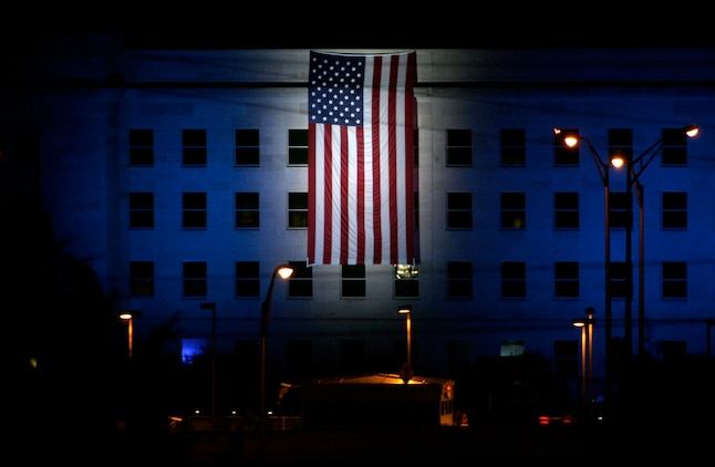 An American flag hangs over the spot where American Airlines Flight 77 crashed into the Pentagon, killing 184 people. The flag was hung on Sept. 10 for the Pentagon Memorial Dedication Ceremony, which took place the following day.   ::r::::n:: ::r::::n::