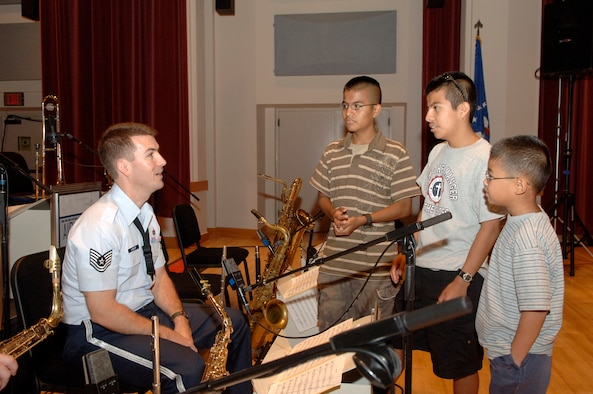 Home-school students Daniel, Luis, and Shawn Boothe talk to Tech. Sgt. Tyler Kuebler, U.S. Air Force Band Airmen of Note, Sept. 5 after a recording session featuring recording artist Kurt Elling. Home-school communities from Fort Meade, Md., Fort Belvoir, Va., Andrews AFB, Md., and Bolling gathered in Gabriel Hall Friday to be part of the Air Force Band's 2008 Jazz Heritage Series. (U.S. Air Force photo by Thomas Dennis)