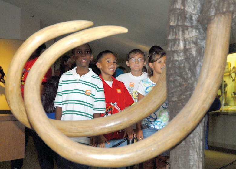 """Children from the Los Angeles Air Force Base Youth Center """"size up"""" next to a mammoth's huge tusks as they enjoy a day at the Page Museum in Hancock Park, famous for the La Brea Tar Pits, Aug. 7. Participants to the 2008 Summer Camp sponsored by the Los Angeles AFB Youth Center enjoyed visits to various local attractions which featured educational venues and physical activities throughout the summer. (Photo by Joe Juarez)"""