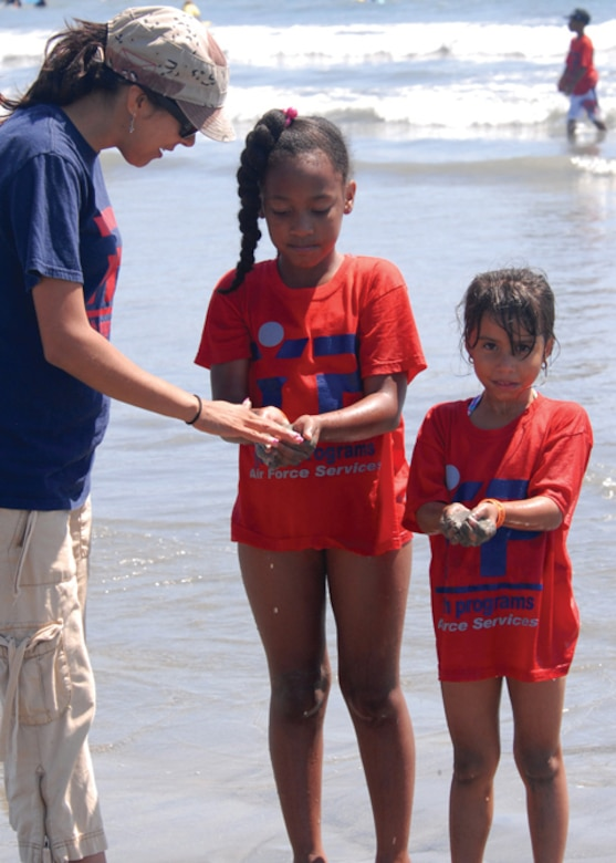 """Ireland Colon (center) and Arelyz Marin (right) hold up scoops of muddy sand for Maricela McIntosh from the Youth Center to check for any """"treasures"""" hidden in the sand during the Seal Beach outing, Aug. 27.  This was the final 2008 Youth Summer Camp event held by the Los Angeles Air Force Base Youth Center. Participants enjoyed visits to various local attractions which featured educational venues and physical activities throughout the summer. (Photo by Joe Juarez)"""
