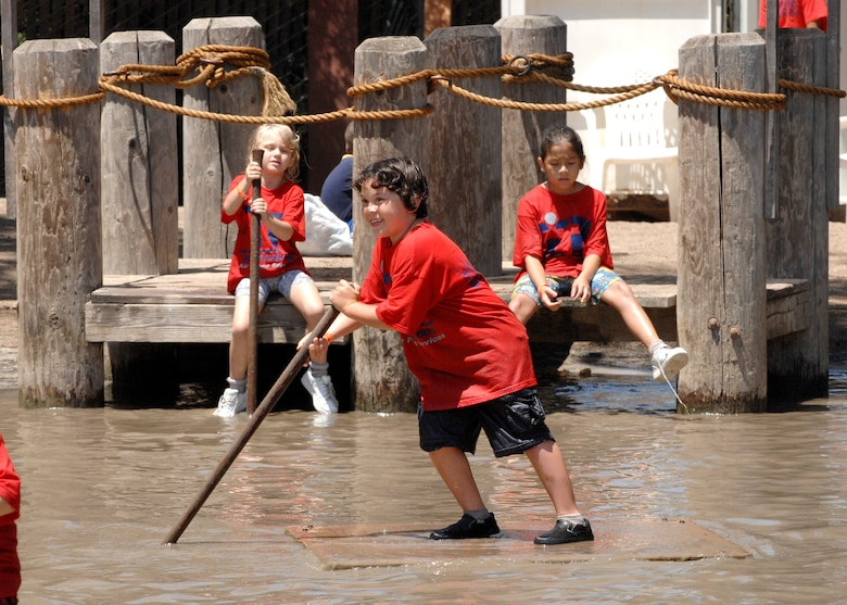 """Jhon Paul Candaso (center) maneuvers a raft across the muddy waters of """"Mud Park"""" as Rachel Beam (left) and Jocelyn Kobayashi (right) wait on the dock during the outing to Huntington Beach Adventure Playground, Aug.6. Participants to the 2008 Summer Camp, sponsored by the Los Angeles Air Force Base Youth Center, enjoyed visits to various local attractions which featured educational venues and physical activities throughout the summer. (Photo by Joe Juarez)"""