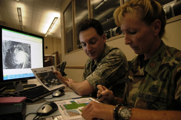 TYNDALL AIR FORCE BASE, Fla. -- Capt. John McMillen from the Air Force Weather Agency at Offutt Air Force Base, Neb., and Maj. Kimberly Pacheco, 601st Air Operations Center weather team chief, monitor the track of Hurricane Ike as they prepare for a briefing at the AOC here Sept. 11.  Weather forecasters with America's AOC continue to work around the clock as the hurricane plows across the Gulf of Mexico toward Texas.  Captain McMillen is one of dozens of active duty members, Guardsmen and Reservists temporary assigned to the AOC and Air Forces Northern in support of hurricane relief operations.  (U.S. Air Force photo/Master Sgt. Brian S. Orban)
