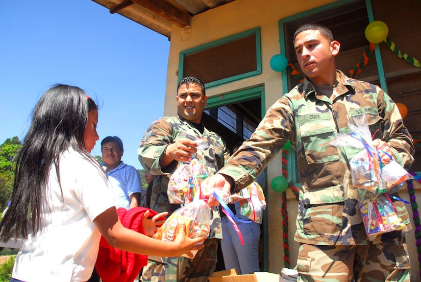 SOTO CANO AIR BASE, Honduras - Air Force Staff Sgt. Edgardo Lebron (left) and Navy Petty Officer 2nd Class Miguel Cruz, Joint Task Force-Bravo, give out candy to children during Children's Day Sept. 10 in Guajiquiro, Honduras. More than 400 children in two towns spent time with servicemembers from JTF-Bravo. (U.S. Air Force photo by Staff Sgt. Joel Mease)