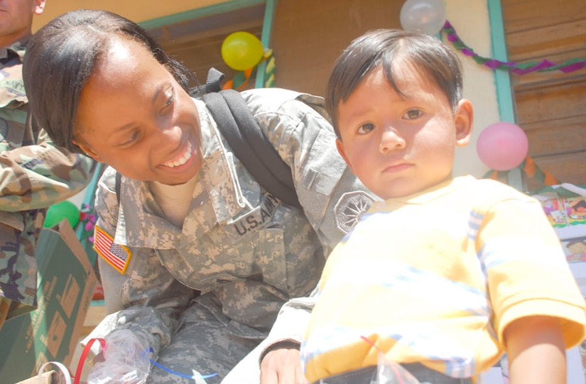 SOTO CANO AIR BASE, Honduras. Army Staff Sgt. Jenise Harris, Joint Task Force-Bravo Civil Affairs, spends time with child during Children's Day Sept. 10 in Guajiquiro, Honduras. More than 400 children in two towns spent time with servicemembers from JTF-Bravo. (U.S. Air Force photo by Staff Sgt. Joel Mease)