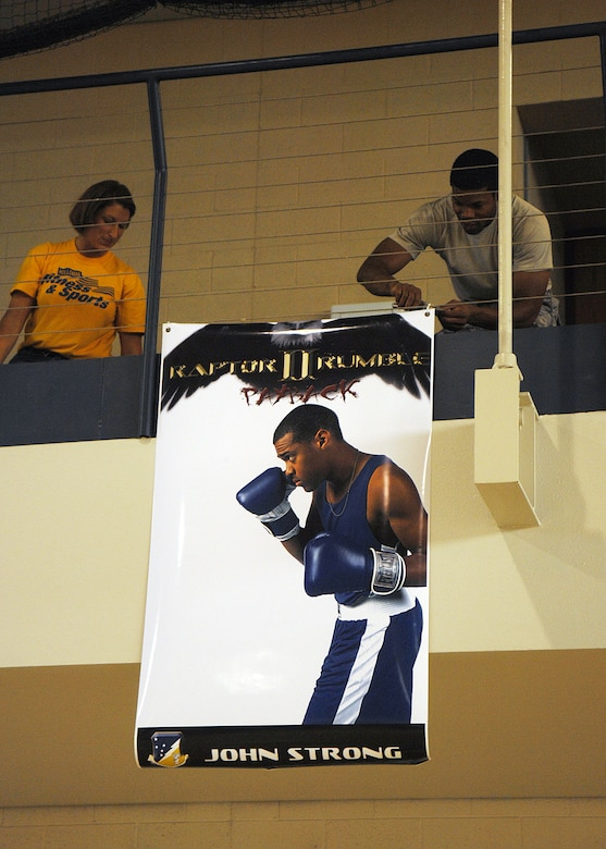 """Volunteers from Team Holloman, help set up the gym for """"Raptor Rumble 2,"""" Sept 12. Volunteers hang photos of the fighters from the gym in preparation for tonight's fights. Raptor Rumble is an annual boxing event held at Holloman for Air Force Service members to participate in amateur boxing. The Raptor Rumble event will be held at the Fitness Center.(U.S. Air Force photo/ Senior Airman Anthony Nelson)"""