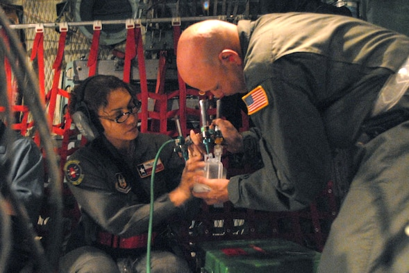 CORPUS CHRISTI INTERNATIONAL AIRPORT, Texas -- Senior Master Sgt. Rowena Sanchez-Reitan and Master Sgt. Mark Juarez, air evacuation tecnicians of the 4th Air Force Reserve Command, 433rd Air Evacuation Squadron, assemble an oxygen system on a C-130E aircraft, September 11, 2008. Little Rock Air Force Base C-130 aircraft and crews are tasked routinely to evacuate possible natural disaster victims to safer locations. (U.S. Air Force photo by Airman 1st Class Steele Briton) (RELEASED)