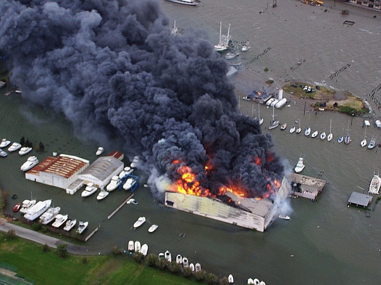 Joint Task Force 129 crew, Jolly 92, flies over a yacht warehouse fire in Galveston, Texas, Sept. 12. The California Air National Guard crew of Jolly 92 rescued six civilians and pets stranded in Galveston. (U.S. Air Force photo by Master Sgt. Wally Bacio)