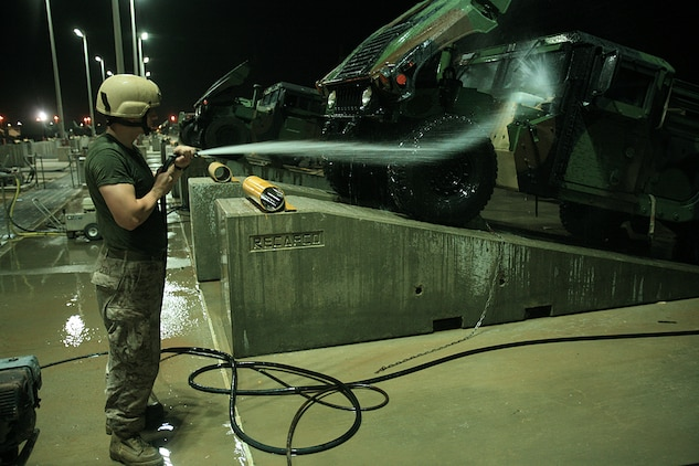 A Marine with the 15th Marine Expeditionary Unit uses a pressure sprayer to clean dirt and debrit from a high mobility multipurpose vehicle.::r::::n::The 15th MEU's vehicles and equipment were required to meet the US Central Command's customs and agricultural standards before being re-embarked aboard ships prior to returning to the Continental United States.(Official USMC photo by Staff Sgt. TG Kessler)(Released)
