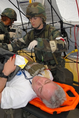 Staff Sergeant Melissa Bennett of the 140th Medical Squadron, Colorado Air National Guard, Aurora Colorado, helps prepare a simulated injured person for surgery.  The medical squadron can see a wide assortment of injuries and must be ready to face the challenges of the unknown at all times.  The 140th Wing is undergoing a Phase II Operational Readiness Inspection this week that they have been training and gearing up for over 3 years. (U.S. Air Force Photo by Tech. Sgt. Wolfram M. Stumpf)  (Released)