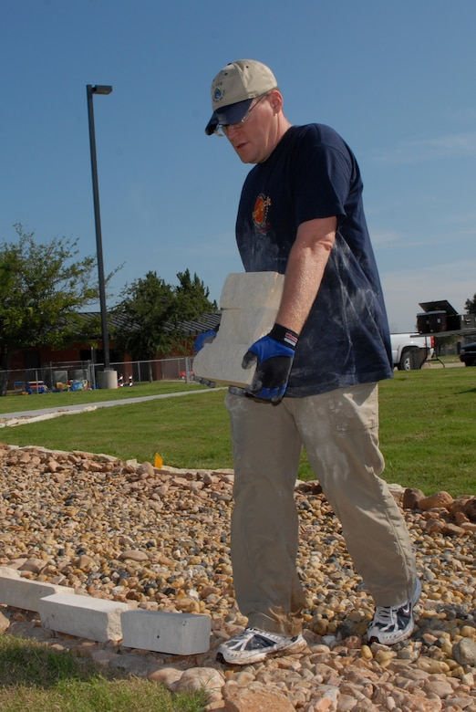 Staff Sgt. Kevin Rodgers, 17th Civil Engineer Squadron readiness flight, carries border rock for the dry riverbed at the Goodfellow School-Age Facility Sept. 13. Taylor Cambre, a Boy Scout from Troop 363, planned and led this undertaking as part of his Eagle Scout service project. Members of the 17 CES volunteered their time to help. (U.S. Air Force photo by Senior Airman Kasabyan Musal)