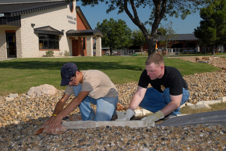 Taylor Cambre, a Boy Scout from Troop 363, and Senior Airman David Le Beau, 17th Civil Engineer Squadron readiness flight, lay border rock for the dry riverbed at the Goodfellow School-Age Facility Sept. 13. Taylor planned and led this undertaking as part of his Eagle Scout service project. Members of the 17 CES volunteered their time to help. (U.S. Air Force photo by Senior Airman Kasabyan Musal)