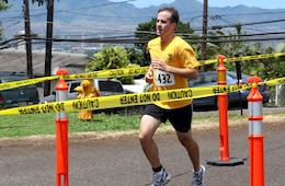 Brian Harrington charges over the finish line finishing the race first with a time of 20:16, during the 12th annuel 5K Grueler Sept. 17.