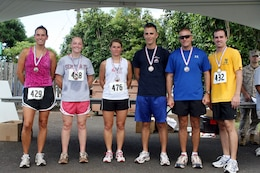 Overall top three runners in the male and female category take their place in the winners circle during the 12th Annual 5K Grueler Sept. 17.  (From left to right and bronze to gold) Liz Ford, Lori Marney Kathryn Huinker, Ronald Shriver, Bruce Jenkins, Brian Harrington.