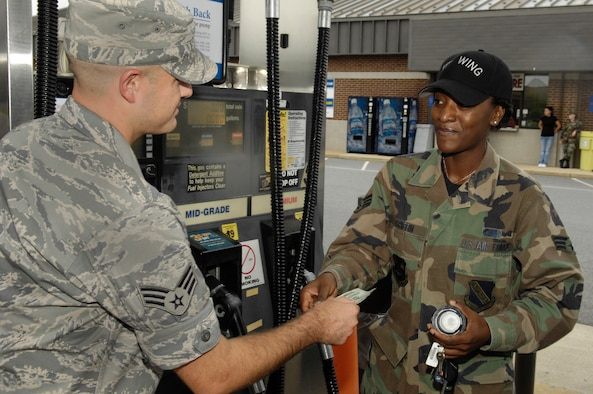 Senior Airman Dan DeCook, Airmen of Distinction events coordniator, hands $20 to Senior Airman Matoya Griffin Sept. 12 at the Bolling Shoppette. The AOD gave away a total of $240 in gas money to Air Force E-4's and below to raise awareness of the council and promote what the council does. (U.S. Air Force illistration by Senior Airmen R. Michael Longoria)