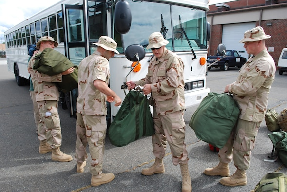Members of the 439th Civil Engineering Squadron get a bag drag going while packing a bus for their trip ahead to Southwest Asia. The Airmen are deploying as firefighters for about four months. (US Air Force photo/Tech. Sgt. Andrew Biscoe)