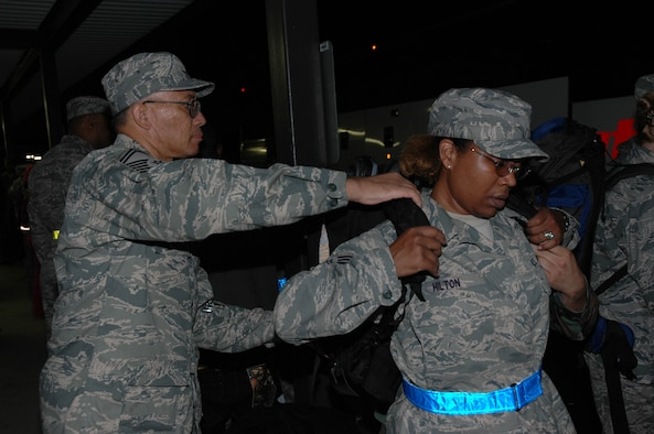 MCGUIRE AIR FORCE BASE, N.J. -- Tech. Sgt. Daphne Hilton, a medical administrator with the Reserve 514th Aeromedical Evacuation Squadron, gets assistance from Senior Master Sgt. Mark G. Johnson, Saturday prior to departing on a 120-day deployment to Iraq. This fall about 50 Citizen Airmen from McGuire AFB are scheduled to participate in four-month deployments supporting the Global War on Terrorism. (U.S. Air Force photo/Master Sgt. Donna T. Jeffries)